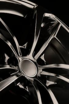 Felga aluminiowa black gloss na ciemnym tle. stylowe i drogie. zbliżenie elementów szprych, zdjęcie pionowe,