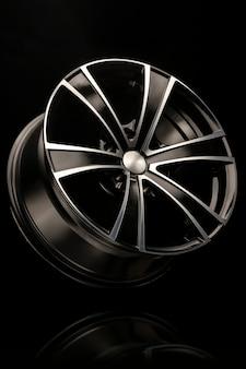 Felga aluminiowa czarna z białym rowkiem, 6 belek do suv-ów i crossoverów, zbliżenie na czarną ścianę. zdjęcie pionowe.