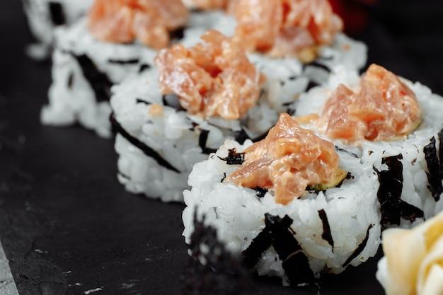 Felix roll z sosem wasabi tuńczyka i marynowanym imbirem na czarnej desce.