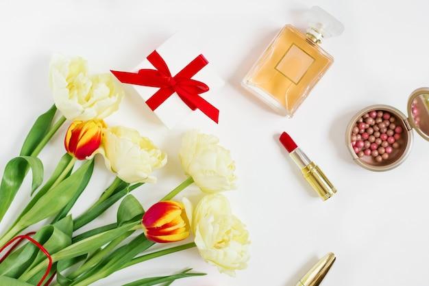 Femenine to kompozycja kobiecej przestrzeni roboczej z prezentami. kosmetyki i bukiet kwiatów tulipanów. widok z góry wiosna.