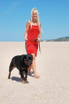 Femme sur la plage promenant son chien