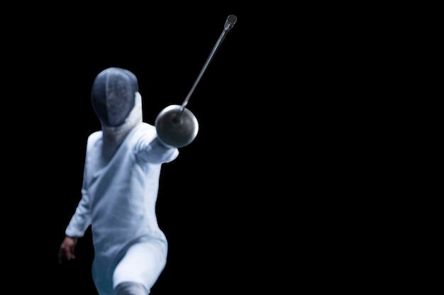 Fencer rusza do przodu z mieczem w dłoni