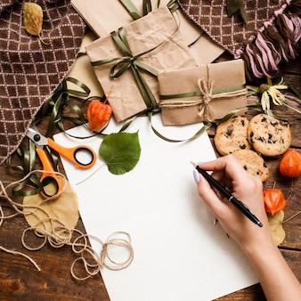 Ferie jesienne i przygotowywanie prezentów, widok z góry. nierozpoznana kobieta pisze listę kontrolną na drewnianym stole w pobliżu małych zapakowanych prezentów, czekoladowych ciastek, nożyczek i opasek leżących na ciepłej, przytulnej kracie