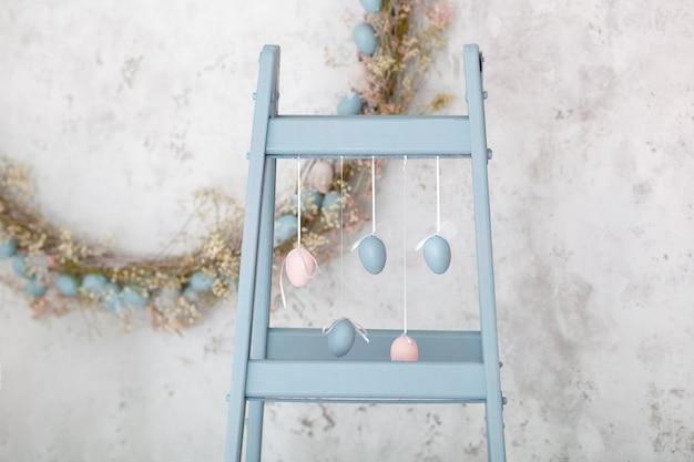 Ferie wielkanocne. home decor niebieska drabina i jaja wianek ściana. dekoracyjny drewniany symbol diy. dekoracyjna drewniana drabina. wystrój pokoju wiosennego. styl rustykalny. uroczystość rodzinna. kolorowe pisanki