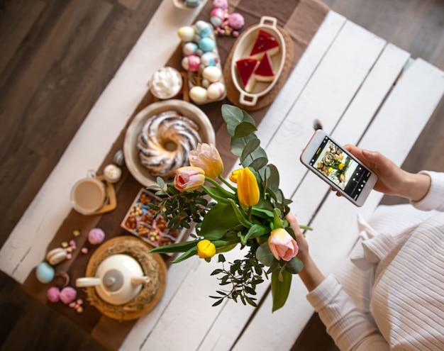 Ferie wielkanocne. zdjęcie z telefonu, pięknie zachowany stół na uroczysty wielkanocny obiad lub śniadanie. pojęcie wartości rodzinnych i święta wielkanocne. widok z góry