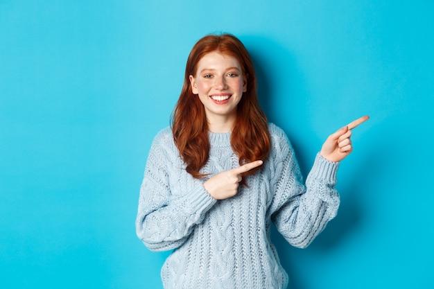 Ferie zimowe i koncepcja ludzi. pretty nastoletnie dziewczyny z rudymi włosami, wskazując palcami w prawo na miejsce na kopię logo, uśmiechając się do kamery, niebieskie tło.