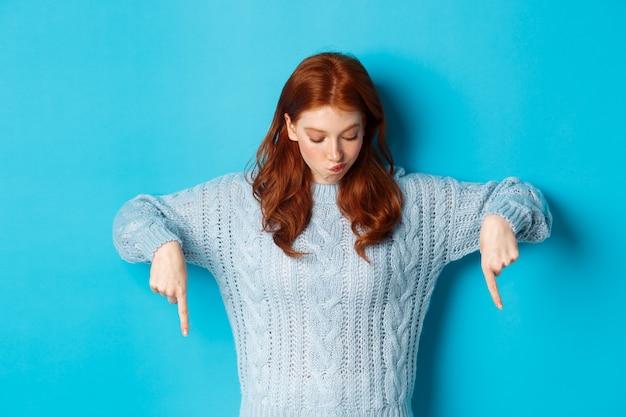 Ferie zimowe i koncepcja ludzi. zaintrygowana ruda dziewczyna, wskazująca i spoglądająca w dół zamyślona, dokonująca wyboru, stojąca na niebieskim tle