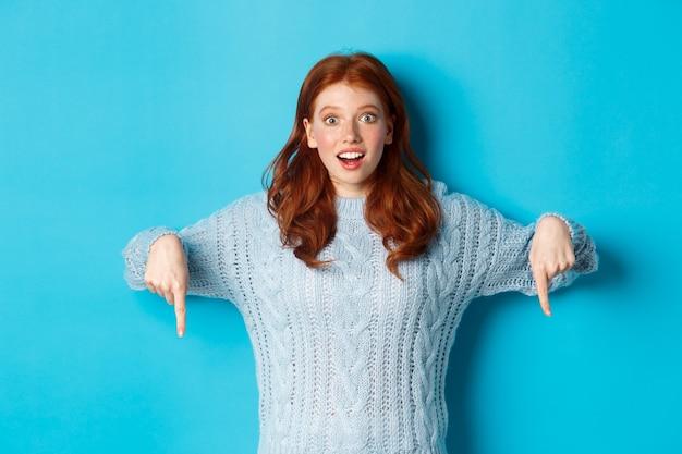 Ferie zimowe i koncepcja ludzi. zaskoczona i podekscytowana rudowłosa dziewczyna, wskazująca palcami w dół i pokazująca promo, wpatrzona w zdumiony aparat, stojąca na niebieskim tle.