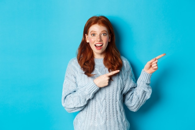 Ferie zimowe i koncepcja ludzie. ciekawa nastolatka w swetrze, wskazując palcami w prawo i wpatrując się w kamerę zdumiona, pokazując ofertę promocyjną, stojąc na niebieskim tle