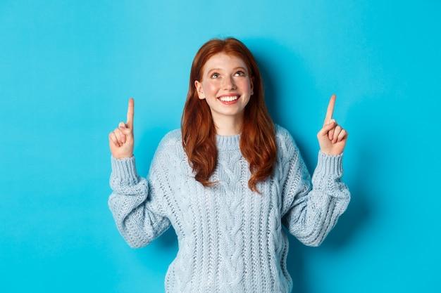 Ferie zimowe i koncepcja ludzie. ładna nastoletnia ruda dziewczyna wskazując palcami w górę, patrząc na górę promo i uśmiechając się rozbawiona, stojąc na niebieskim tle.