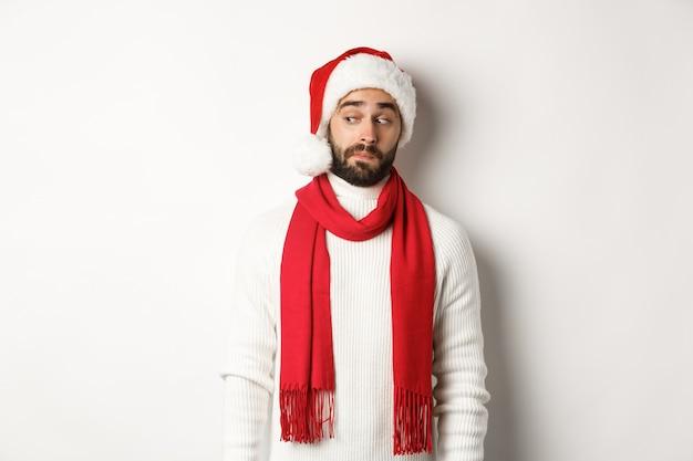 Ferie zimowe i koncepcja partii nowy rok. ciekawy facet zerkający na lewy baner z logo, stojący w czapce świętego mikołaja, świętujący boże narodzenie, stojący na białym tle