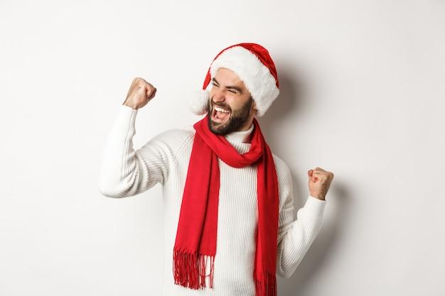 Ferie zimowe i koncepcja partii nowy rok. przystojny brodaty mężczyzna w santa hat wygrywa nagrodę, osiąga cel i świętuje, robi pięść i mówi tak, białe tło.