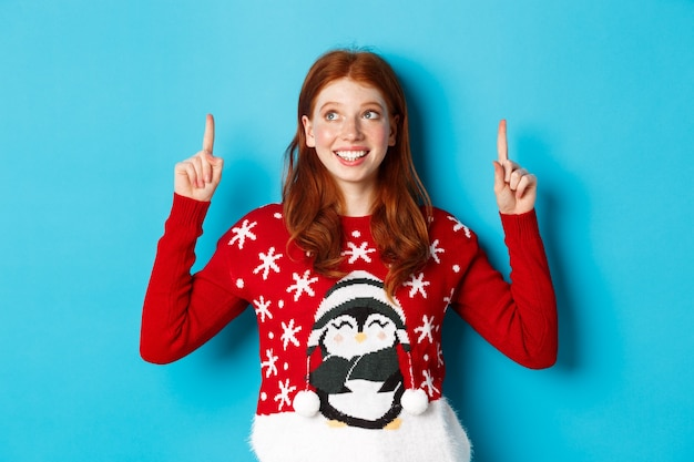 Ferie zimowe i koncepcja uroczystości. wesoła nastolatka z rudymi włosami, rozmarzona patrząc na logo, wskazująca palcami w górę, pokazująca reklamę, stojąca na niebieskim tle.