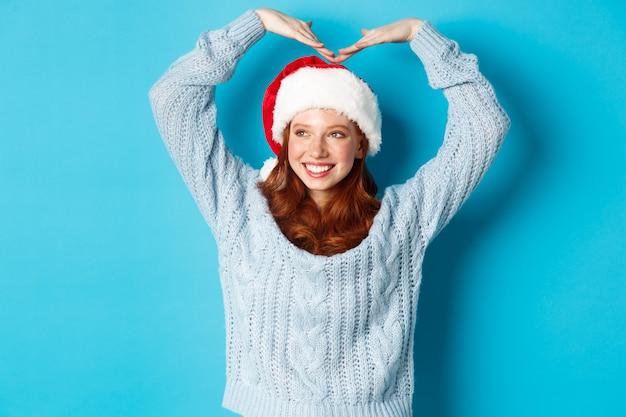 Ferie zimowe i koncepcja wigilii. śliczna rudowłosa nastolatka w santa hat i swetrze, czyniąc znak serca i uśmiechnięta, życząc wesołych świąt, stojąc na niebieskim tle.