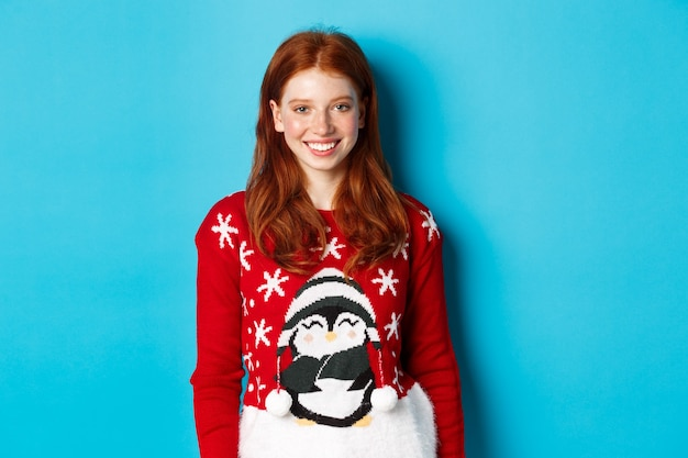 Ferie zimowe i koncepcja wigilii. śliczna uśmiechnięta nastolatka z rudymi włosami, ubrana w śmieszny świąteczny sweter, stojąca na niebieskim tle.