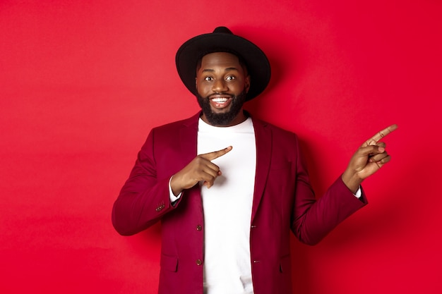 Ferie zimowe i koncepcja zakupów. stylowy afroamerykanin wskazujący palcami na miejsce na logo, stojący na czerwonym tle