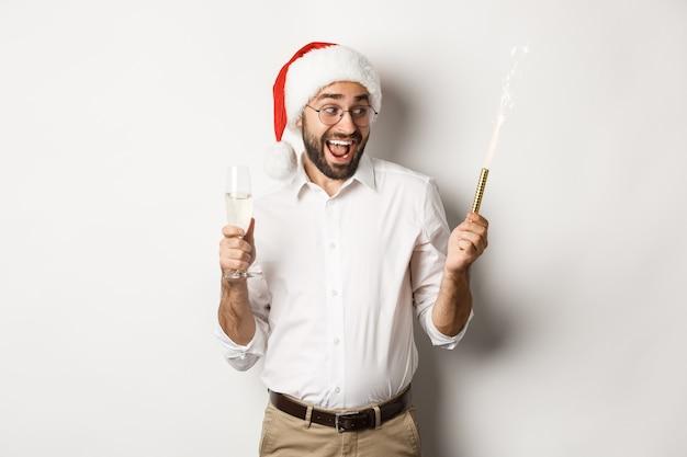 Ferie zimowe i uroczystości. podekscytowany mężczyzna świętuje sylwestra z fajerwerkami błyszczy i pije szampana, ubrany w kapelusz santa, białe tło.