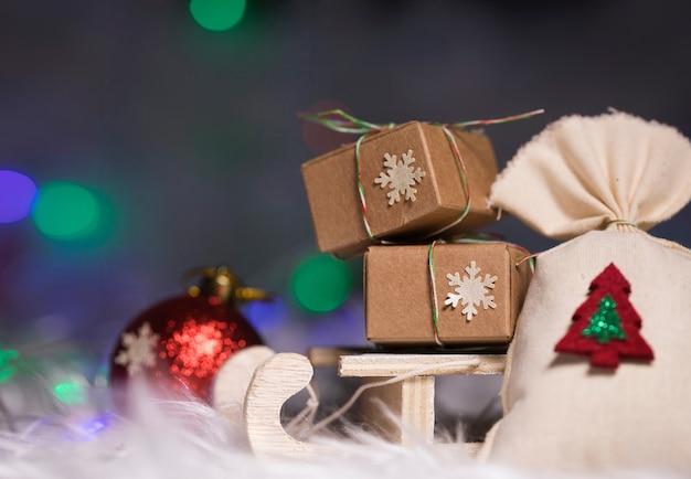 Ferie zimowe tło: prezenty świąteczne na mini drewniane sanie. zbliżenie