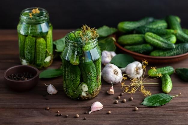 Fermentacja ogórków w szklanych słoikach. surowe ogórki, koperkowe kwiaty, liść wiśni, liść chrzanu, przyprawy i zioła na drewnianym stole
