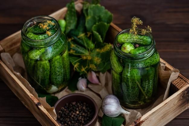 Fermentacja ogórków w szklanych słoikach. surowe ogórki, kwiaty koperku, liść wiśni, liść chrzanu, przyprawy i zioła na tacy