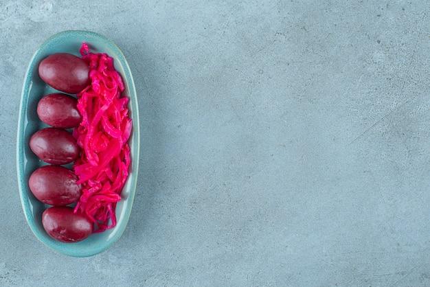 Fermentowana czerwona kapusta kiszona ze śliwkami na talerzu, na niebieskim stole.