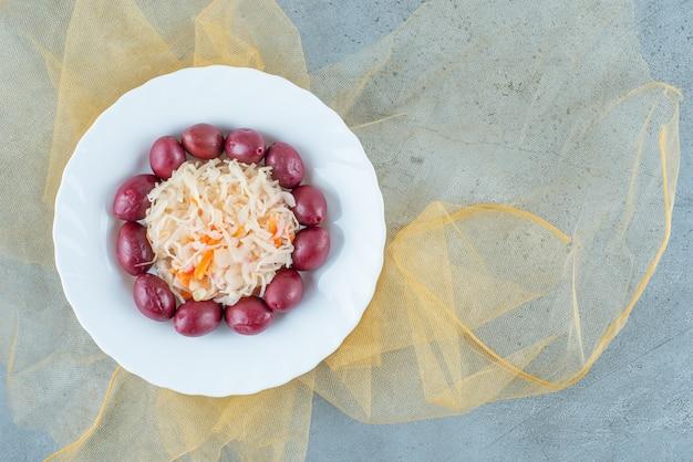 Fermentowana kapusta kiszona ze śliwkami na talerzu na tiulu, na niebieskim stole.