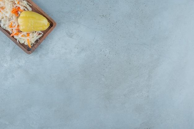 Fermentowana papryka i kiszona kapusta na desce, na niebieskim stole.