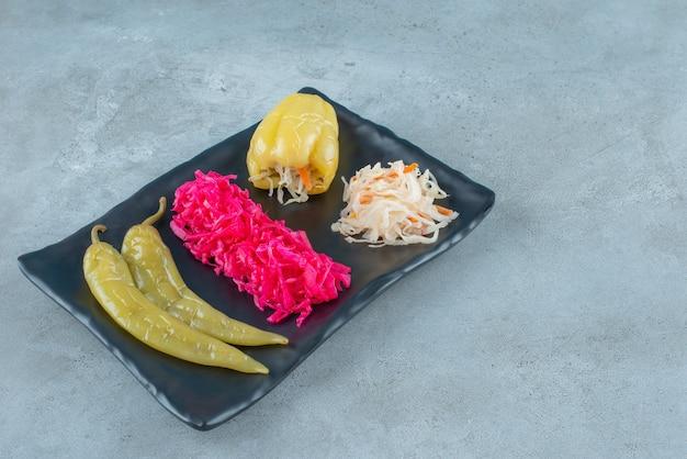 Fermentowana papryka i kiszona kapusta na plastikowym talerzu, na niebieskim stole.