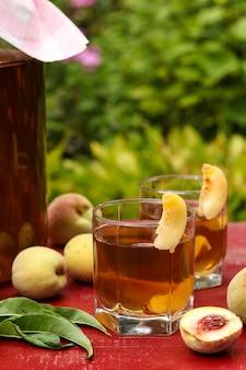 Fermentowana surowa herbata kombucha z brzoskwinią, letni zdrowy napój detoksykacyjny w słoiku i dwie szklanki, orientacja pionowa