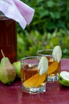 Fermentowana surowa herbata kombucha z gruszkami, letni zdrowy napój detoksykacyjny w słoiku i dwie szklanki, orientacja pionowa