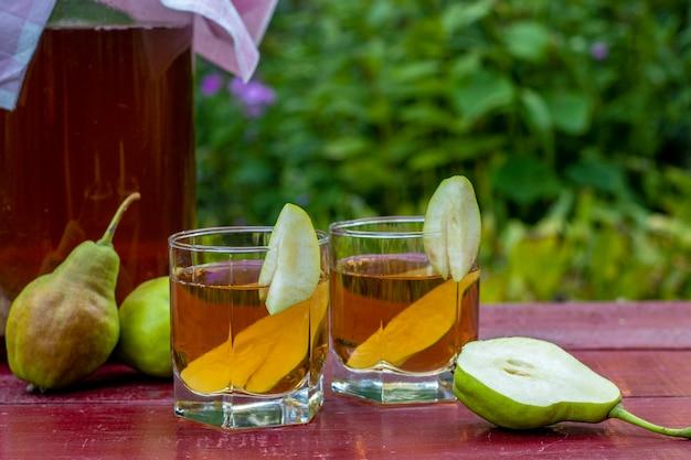 Fermentowana surowa herbata kombucha z gruszkami, letni zdrowy napój detoksykacyjny w słoiku i dwie szklanki
