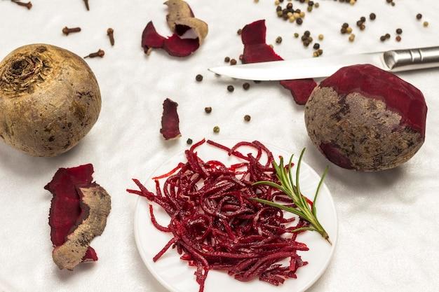 Fermentowane buraki na talerzu. buraki i nóż. obieranie warzyw. zdrowa żywność zimowa. domowe produkty fermentacji. biała powierzchnia. widok z góry