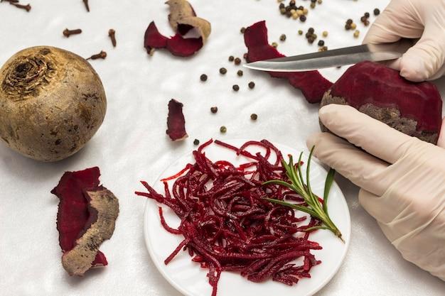 Fermentowane buraki na talerzu. buraki i nóż. ręce w rękawiczkach do obierania buraków. zdrowa żywność zimowa. domowe produkty fermentacji. biała powierzchnia. widok z góry