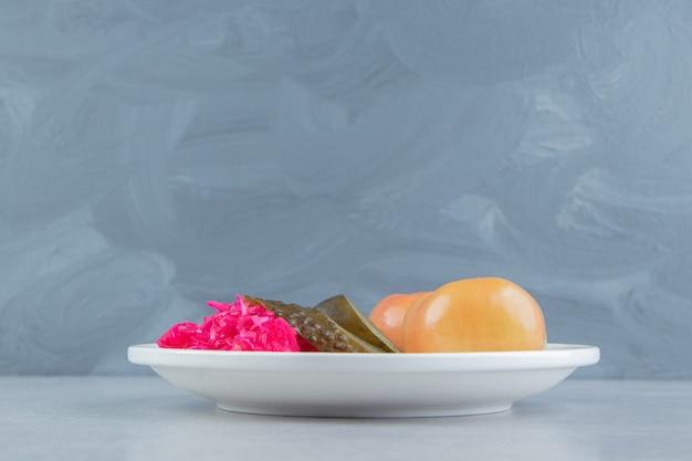 Fermentowane warzywa i kapusta kiszona na białym talerzu.