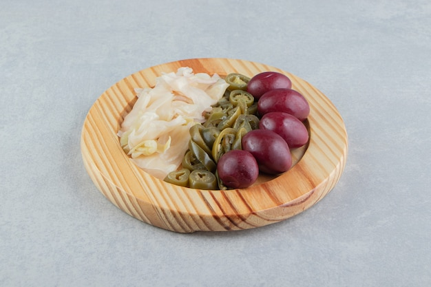Fermentowane warzywa umieszczone na drewnianym talerzu.
