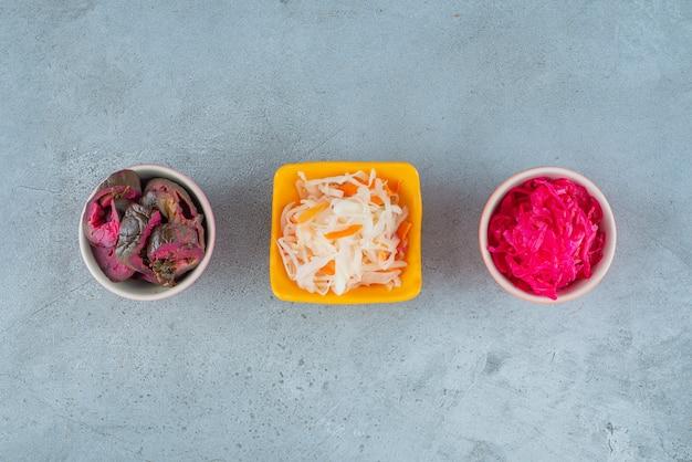 Fermentowane warzywa w misce, na marmurowym stole.