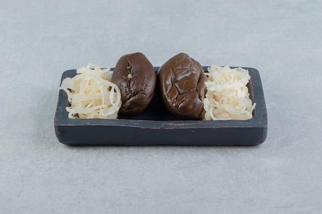 Fermentowany bakłażan i kiszona kapusta na ciemnym talerzu.