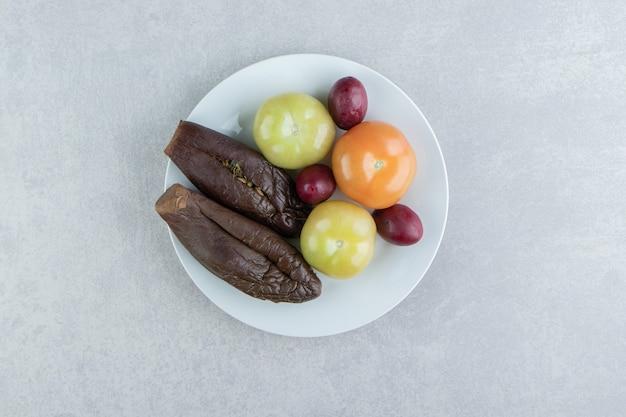 Fermentowany bakłażan i pomidory na białym talerzu.