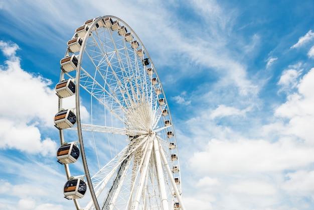 Ferris koło przeciw niebieskiemu niebu z chmurami