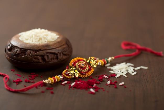 Festiwal indyjski: tło raksha bandhan z eleganckimi rakhi, rice grains i kumkum. tradycyjna indyjska opaska na nadgarstek będąca symbolem miłości między braćmi i siostrami.