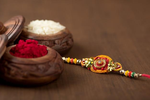 Festiwal indyjski: tło raksha bandhan z eleganckimi rakhi, rice grains i kumkum.