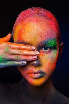 Festiwal kolorów holi. portret piękna modelka z kolorowy proszek makijaż pozowanie. piękna kobieta z tęczowym makijażem. streszczenie kolorowy makijaż sztuki, upraw