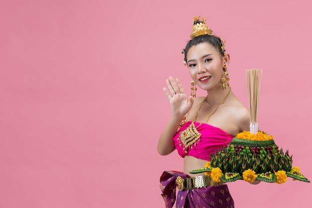 Festiwal loy krathong. kobieta w tradycyjnym tajskim stroju gospodarstwa zdobione pływające