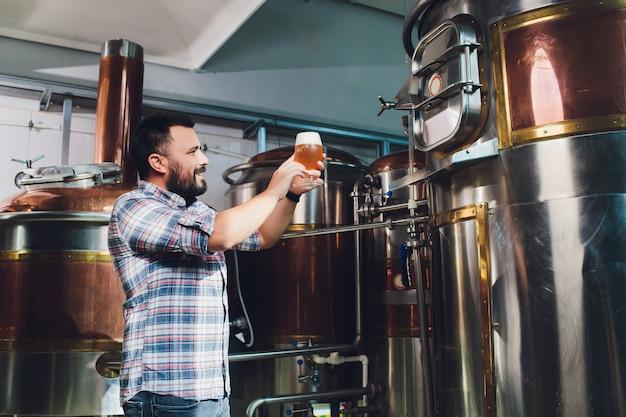 Festiwal oktoberfest. degustacja świeżo parzonego piwa. browar trzyma szklankę z piwem rzemieślniczym. koncepcja browaru. człowiek z piwem kubek. alkohol. męski browar trzyma szkło z piwem. święto oktober. barman. piwowar.