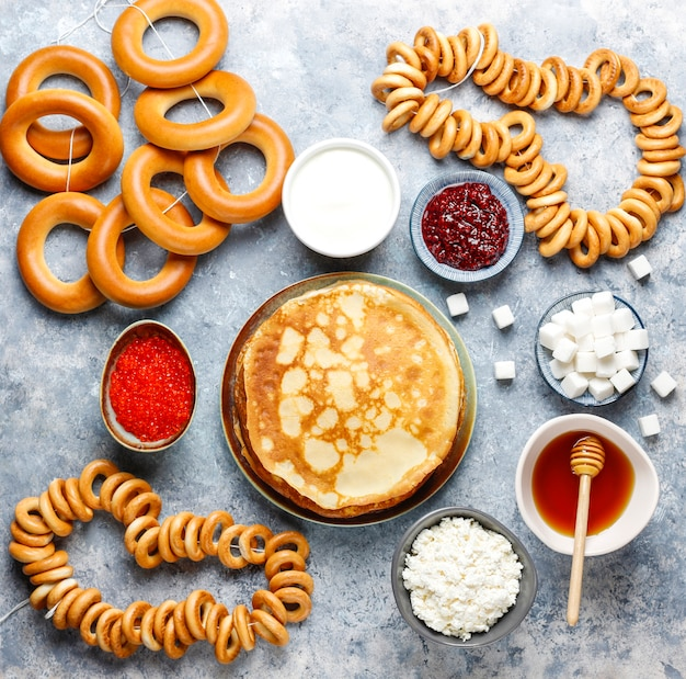 Festiwalowy posiłek zapusty maslenitsa. rosyjskie bliniowe naleśniki z dżemem malinowym, miodem, świeżą śmietaną i czerwonym kawiorem, kostkami cukru, twarogiem, bublikami na świetle
