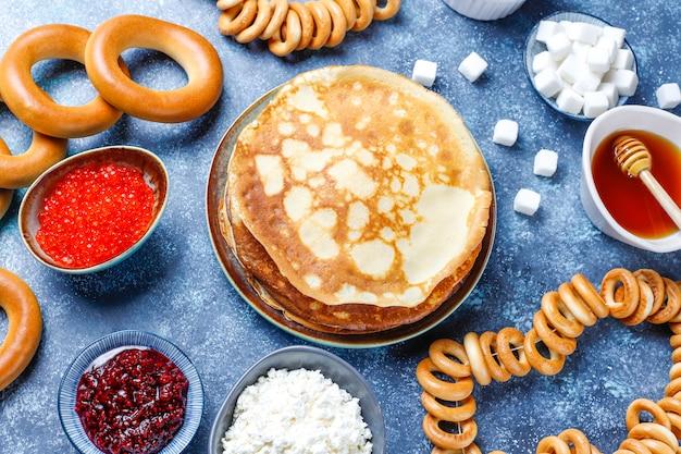Festiwalowy posiłek zapusty maslenitsa. rosyjskie bliniowe naleśniki z dżemem malinowym, miodem, świeżą śmietaną i czerwonym kawiorem, kostkami cukru, twarogiem na ciemności