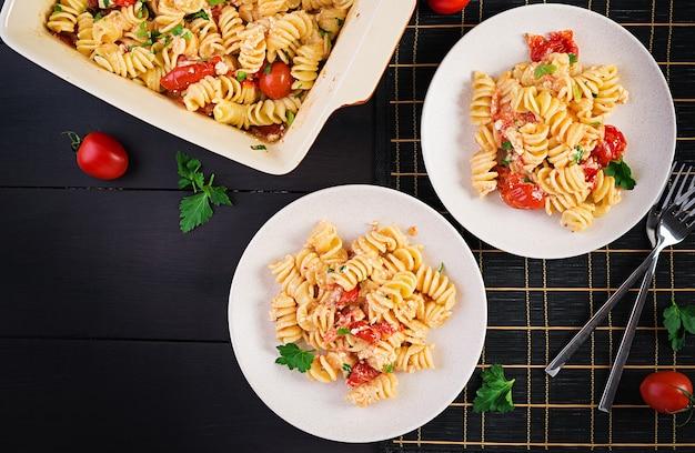 Fetapasta. popularny przepis na zapiekany makaron feta z pomidorkami koktajlowymi, serem feta, czosnkiem i ziołami. nakrycie stołu. widok z góry, powyżej, miejsce na kopię.