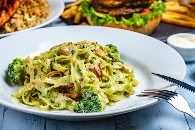 Fettuccine makaron brokuły kurczak kremowy sos przyprawy pieprz widok z boku