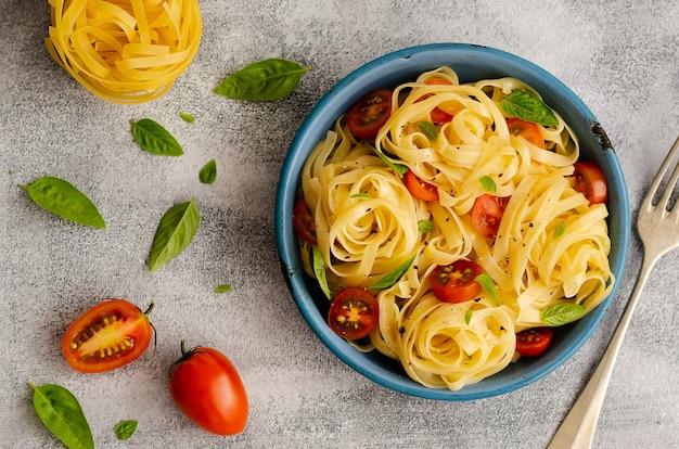 Fettuccine z pokrojonymi pomidorkami cherry i listkami bazylii