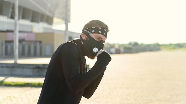 Fighter man trening bokserski poncz na miejskiej ulicy portret fitness man bokserski odkryty na czarno